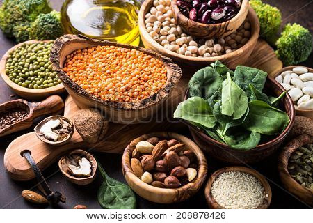 Healthy vegan food assortment. Leguminous, nuts, broccoli, spinach and seeds on dark rusty table.