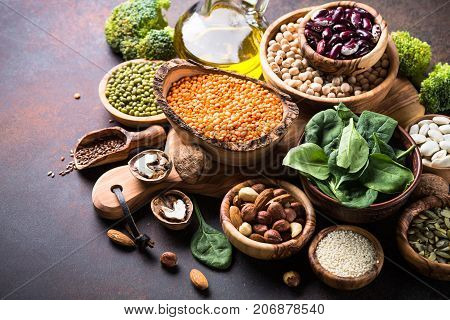 Healthy vegan food assortment. Leguminous, nuts, broccoli, spinach, oil  and seeds on dark rusty table with copy space.