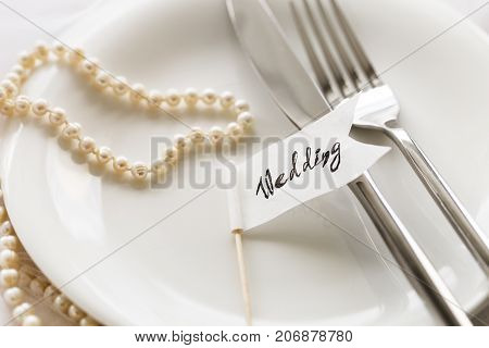 Close-up of white small flag with word Wedding lying on white plate with silverware and pearl necklace.