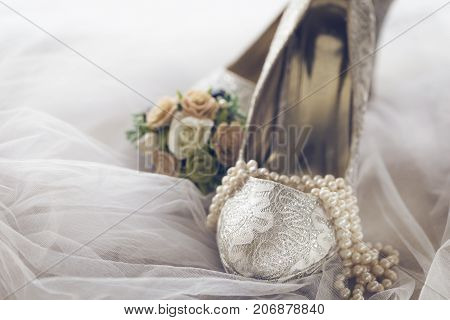 Closeup of gentle arrangement of bridal lace shoes with pearl necklace and bouquet on white veil.