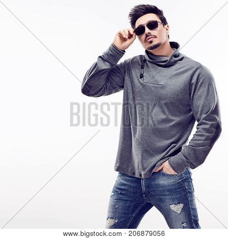 Handsome Sexy young Fashion guy in Trendy Sunglasses. Sporty Confident Brunette Bearded man. Autumn Outfit, Stylish Hairstyle, fashionable gray jumper. Studio fashion pose on white background