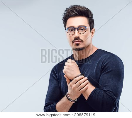 Handsome young Fashion man. Autumn Elegant Outfit, Trendy Glasses. Portrait Sporty Confident Brunette Bearded guy in blue jumper, Stylish Hairstyle. Studio fashionon gray background