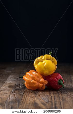 different kinds of hot chili peppers on table on black background and copyspace