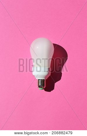 Fluorescent light bulb on a bright pink background.