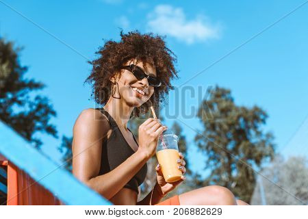 African-american Woman In Bleachers With Juice