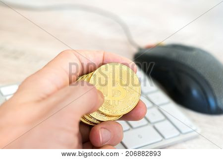 Several Golden Bitcoins In A Hand