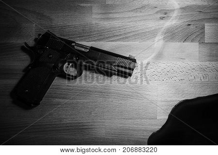 gun and blood on wooden table. black and white. robbery, murder, crime and security concept