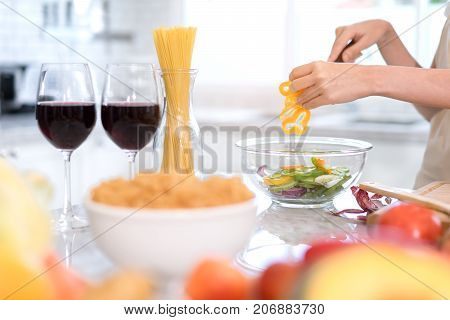 Closeup Young woman cutting slice vegetables making salad heathy food with fruits cooking menu for dinner with wine glass in kitchen at home