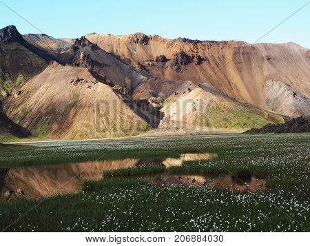 Colored mountains reflected in water Landmannalaugar valley Iceland