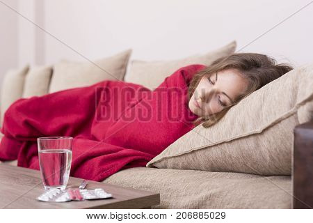 Sick woman covered with a blanket lying in bed with high fever and a flu. Pills and glass of water on the table