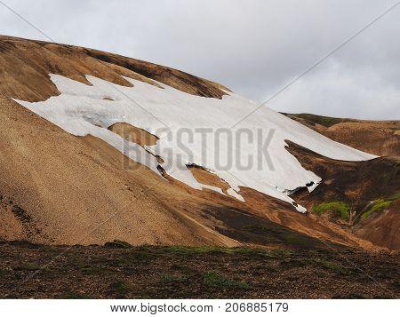 Snow on the yellow mountain valley of the Landmannalaugar Iceland