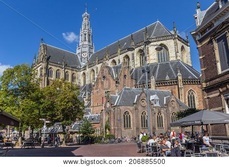 HAARLEM, NETHERLANDS - SEPTEMBER 03, 2017: People enjoying the sun at the St. Bavo church in the center of Haarlem Netherlands