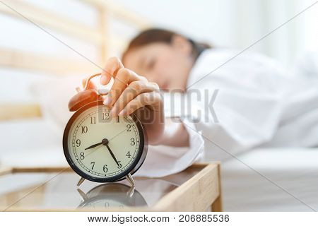 Young asian woman press the button snooze wake up alarm clock alert in the morning and sleeping lazy next on bedroom at home