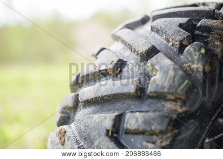 Dirty protector tire. Mud tire ATV. Selective focus.