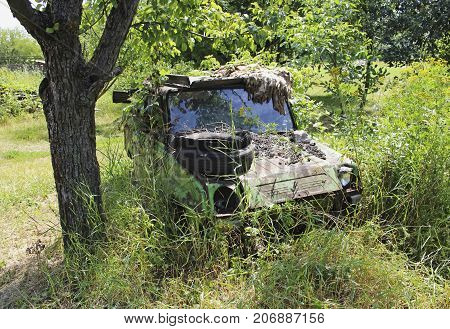 An old abandoned green car without a headlight with a tire on the hood against a background of green grass
