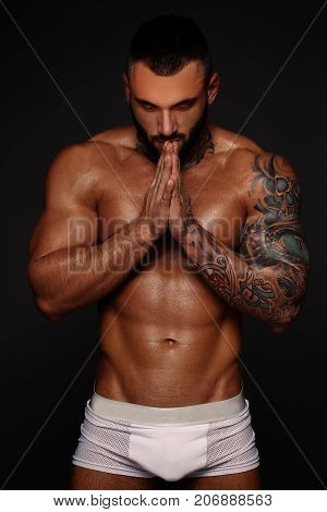 Sexy closeup portrait of handsome topless male model with beautiful eyes. Sexy man or muscular macho, bodybuilder, with muscle torso, body with six packs and abs poses on black background in white panties.