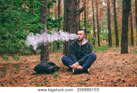 Vape man. brutal bearded young man having rest in forest. Man sitting under tree. Lifestyle. poster