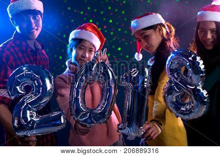 Young Asian group man and women holding balloon new year 2018 christmas pary in midnight december at nightclub countdown luxury