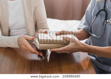 Nurse And Senior Patient With Books