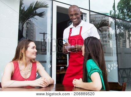 Laughing african american waiter welcoming guests in restaurant