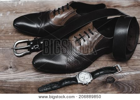 shoes with belt and watch in wooden table