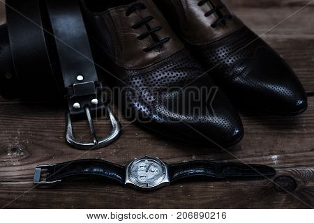fashion shoes with belt and watch in wooden table