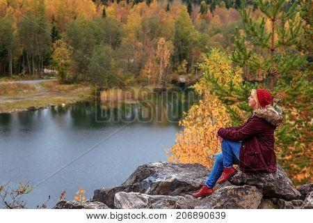 Girl tourist looks at mountain lake in Marble Canyon. Autumn in Karelia Russia.