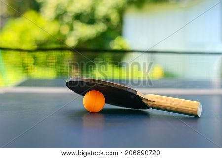 Table tennis table with racket and orange ball on a blue table with net installed on backyard of the house in Australia shallow DOF focus on ball