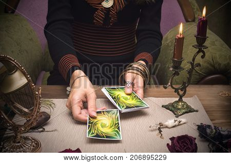 Tarot cards on wooden table and fortune teller hands. Reading future.