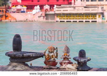 Hindu Religion Symbols On The Bank Of The Ganges River, Sacred Waters. Shiva Sculpture And Lingam. D