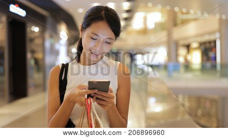 Woman sending sms on cellphone with shopping bags