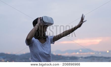 Woman watching virtual reality device in sunset time
