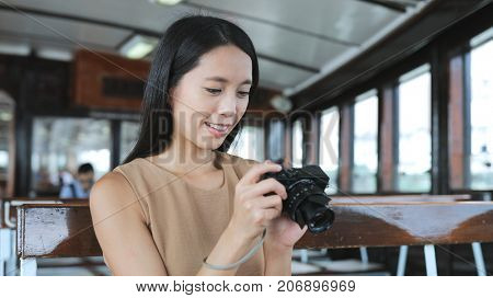 Woman taking photo with digital camera on ferry