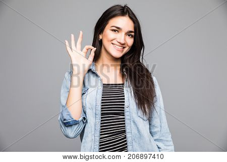 Portrait Of Young Cheerful Smiling Woman Showing Okay Gesture, With Copyspace, Over Grey