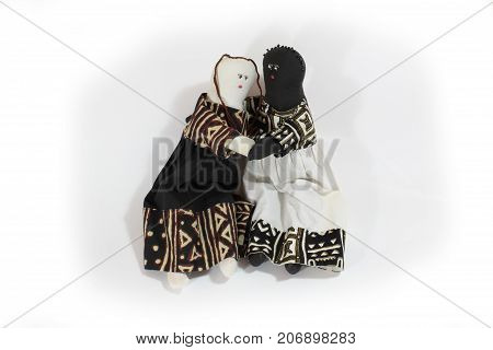 Black doll and white doll embrace concept forgiveness, reconciliation, isolated on white