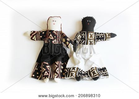 Black doll and white doll hand to hand concept division, difference, unity, isolated on white