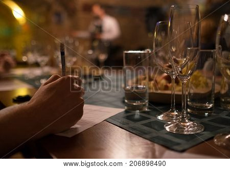 Wine tasting sommelier writes something in note table.