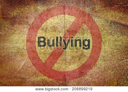 Word Bullying written over a traffic sign on grunge background