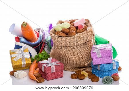 Burlap sack with traditional sweets for the Dutch holiday 'Sinterklaas' and colorful gifts over white. Festive concept with copy space.