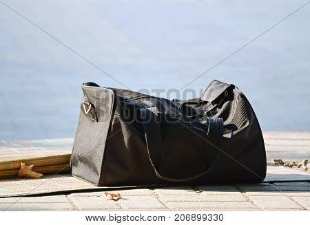Closeup of a black tourist bag on the pavement