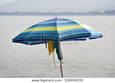 Closeup of one blue parasol and hanging clothes on the beach