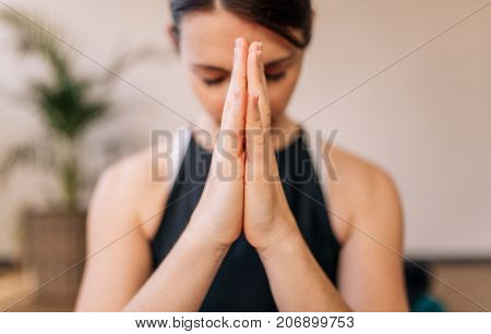 Close up of woman hands joined. Female meditating with her hands joined indoors. Namaste yoga pose meditating breathing and relaxing.