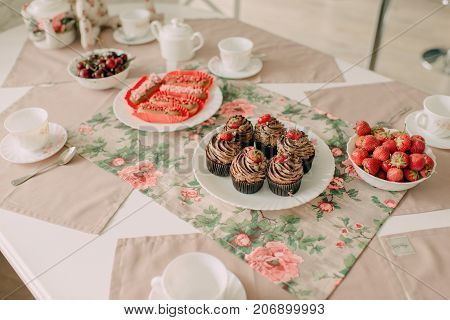a plate of cupcake with strawberries on a server table