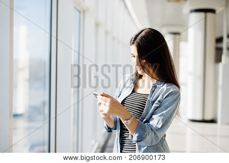 Pretty Girl Typing On Phone And Looking Outdoors Through A Window