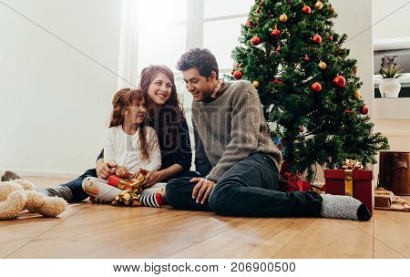 Family sitting beside Christmas tree opening gifts. Small family having happy time together on Christmas.