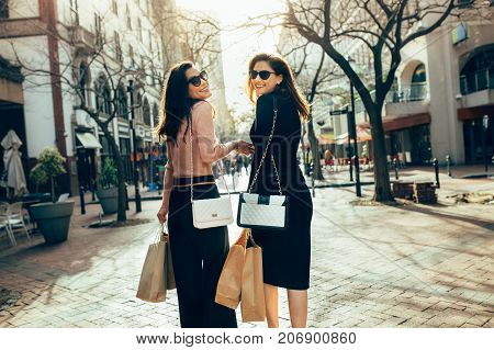 Female Shoppers Carrying Shopping Bags On City Street