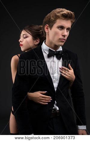 Sexy gentleman in a siut and bow-tie with his girl-friend embracing him cropped isolated shot on black background