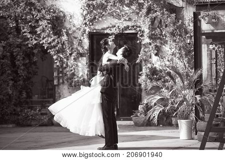 asian newly wed bride and groom celebrating marriage outside a building black and white.