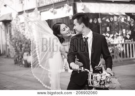 romantic asian newly wed couple having fun riding a bicycle together black and white.