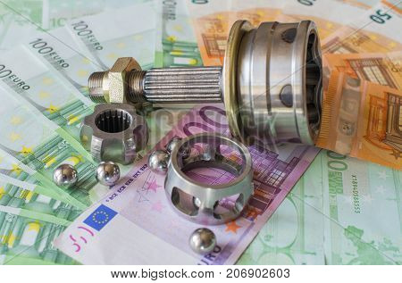 Details of the car on the background of banknotes. Disassembled the CV joint. Selective focus.
